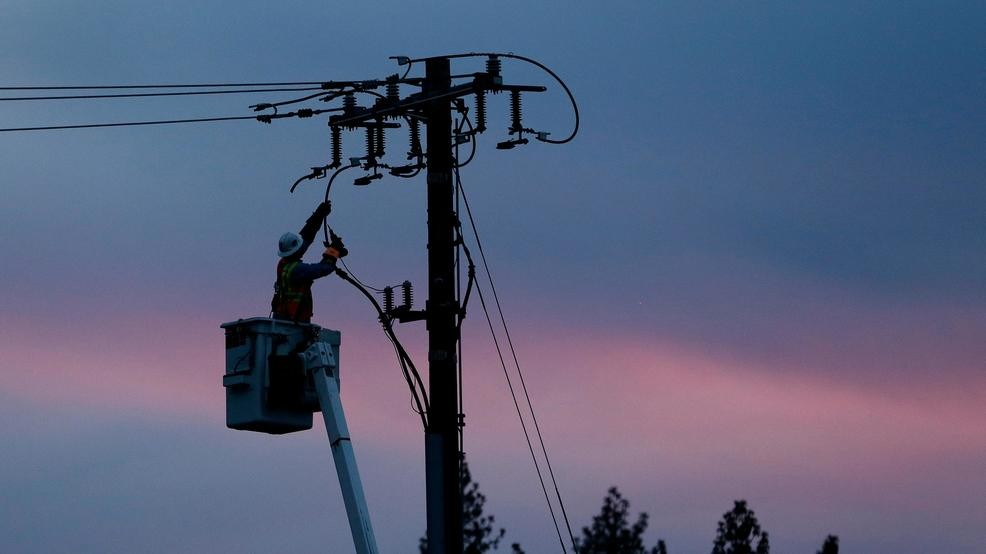(Image: a lineman works to repair a power line in fire-ravaged Paradise, California) (Story: Regulators approve PG&E wildfire plan, statewide power shutoff rules)
